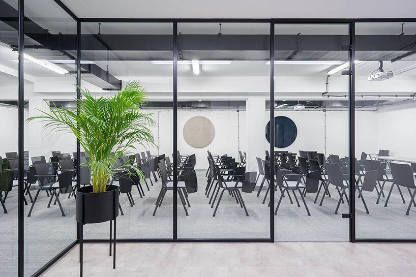 nowoczesna przestrzeń biurowa MDD Work Together sala konferencyjna zczarnymi krzesłami oddzielona przeszklonymi ścianami zczarną ramką
