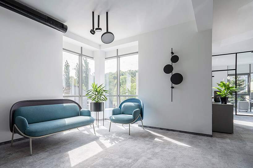 nowoczesna przestrzeń biurowa MDD Work Together niebieska sofa ifotel wbiałej przestrzeni zszarą podłogą