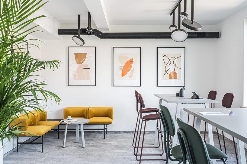 nowoczesna przestrzeń biurowa MDD Work Together żółta ławeczka narożna przy białym stoliku obok wysokich biurek zkolorowymi krzesłami