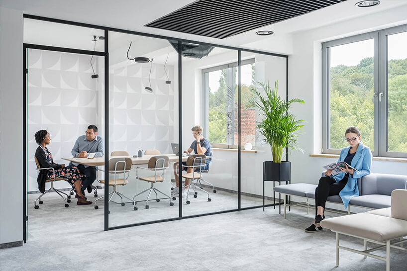 nowoczesna przestrzeń biurowa MDD Work Together mała sala konferencyjna zkrzesłami na kółkach oddzielona szklaną ściną zczarną ramką