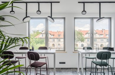 nowoczesna przestrzeń biurowa MDD Work Together białe wyższe biurka z krzesłami na tle okien z widokiem na kamienice