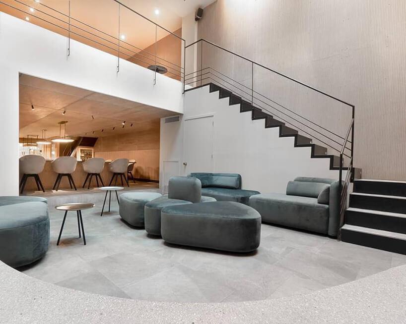meble BoConcept wrestauracji Atomix wNowym Jorku szare sofy isiedziska na tle ciemnych schodów