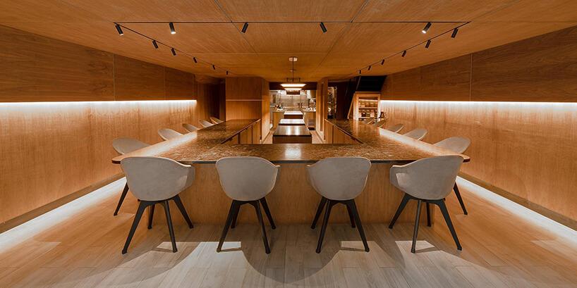meble BoConcept wrestauracji Atomix wNowym Jorku drewniane wnętrze ze stołem otoczonym białym krzesłami