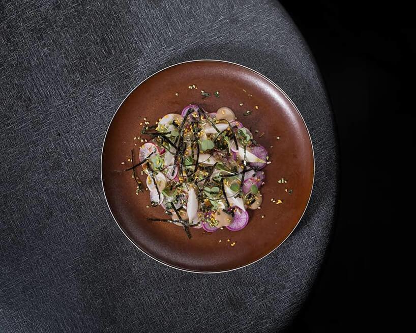 meble BoConcept wrestauracji Atomix wNowym Jorku eleganckie danie na szarym okrągłym stole