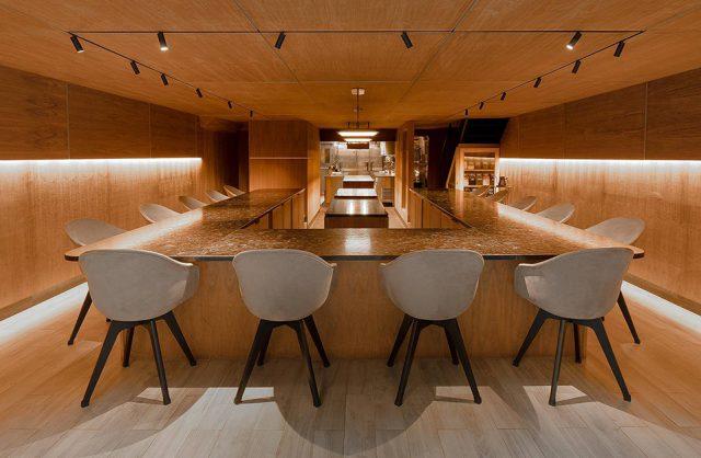 meble BoConcept w restauracji Atomix w Nowym Jorku drewniane wnętrze ze stołem otoczonym białym krzesłami