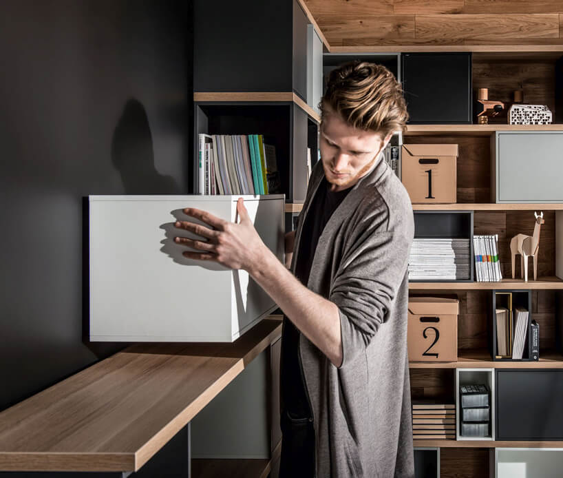 mężczyzna ustawiający biała szafkę zkompletu mebli Balance od VOX