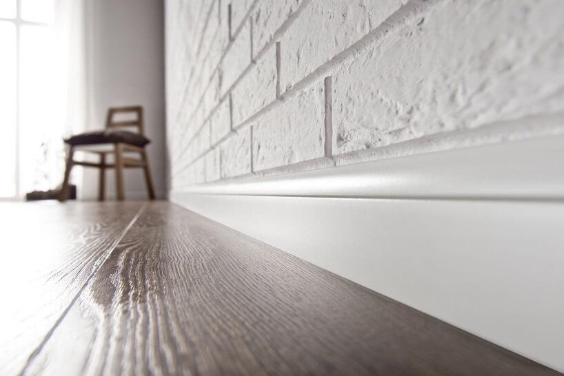 biała listwa przypodłogowa Estilo od VOX przy ciemnej drewnianej podłodze