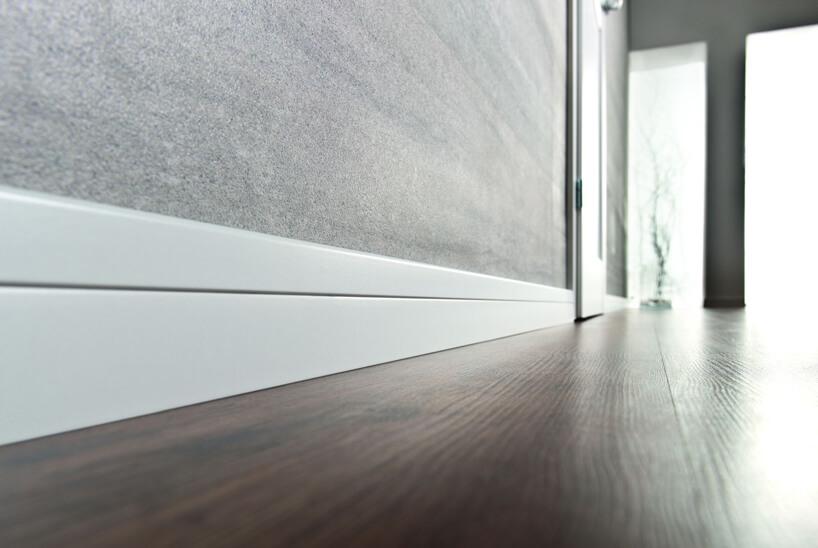 biała listwa przypodłogowa Estilo od VOX przy ciemnej drewnianej podłodze iszarej ścianie
