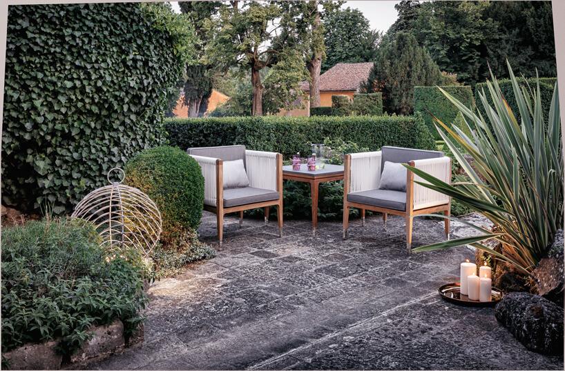 dwa drewniane fotele ogrodowe zbiałymi siedziskami wotoczeniu roślin na ciemny kamieniu