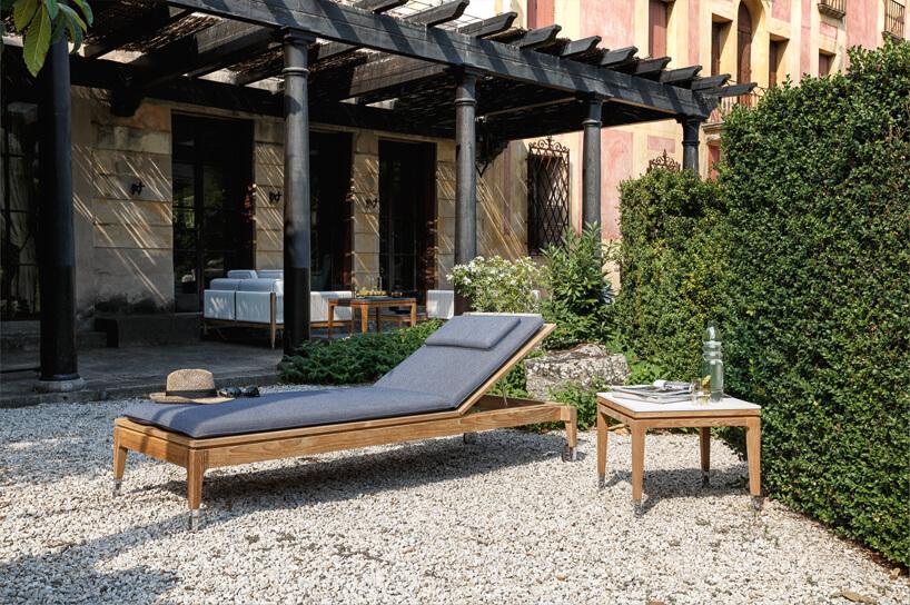 drewniany leżak ogrodowy zdrewnianym stolikiem na kamiennym tarasie