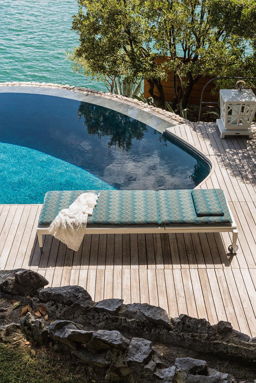 zielona drewnaina leżanka ogrodowa na drewnianym otoczeniu basenu