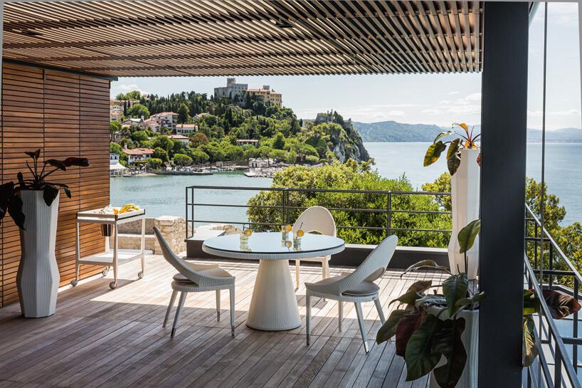 biały elegancki zestaw ogrodowy na zadaszonym drewnianym tarasie na tle śródziemnomorskiego morza iroślin