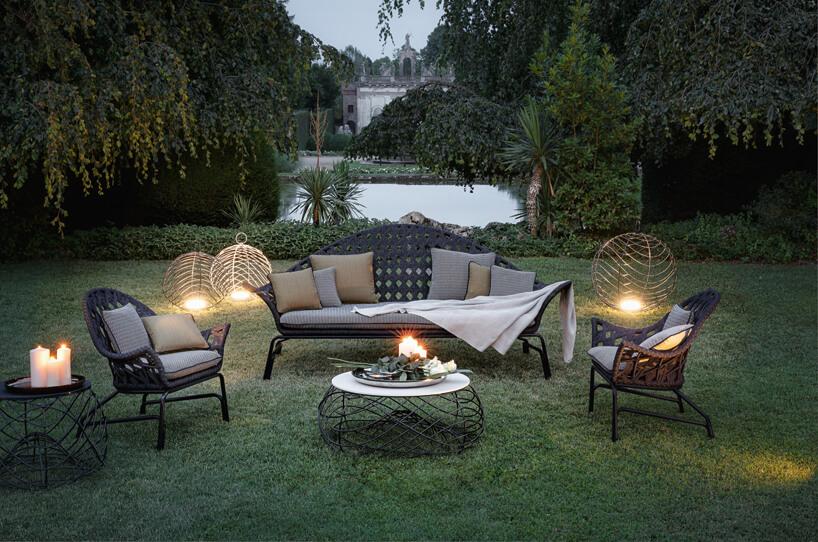 elegancki komplet mebli ogrodowych wogrodzie wieczorem oświetlony świecami