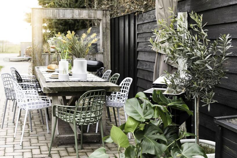 zestaw ogrodowy zdużym stołem ikrzesłami wotoczeniu drewnianego tarasu