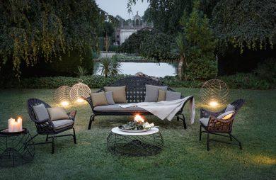 elegancki komplet mebli ogrodowych w ogrodzie wieczorem oświetlony świecami