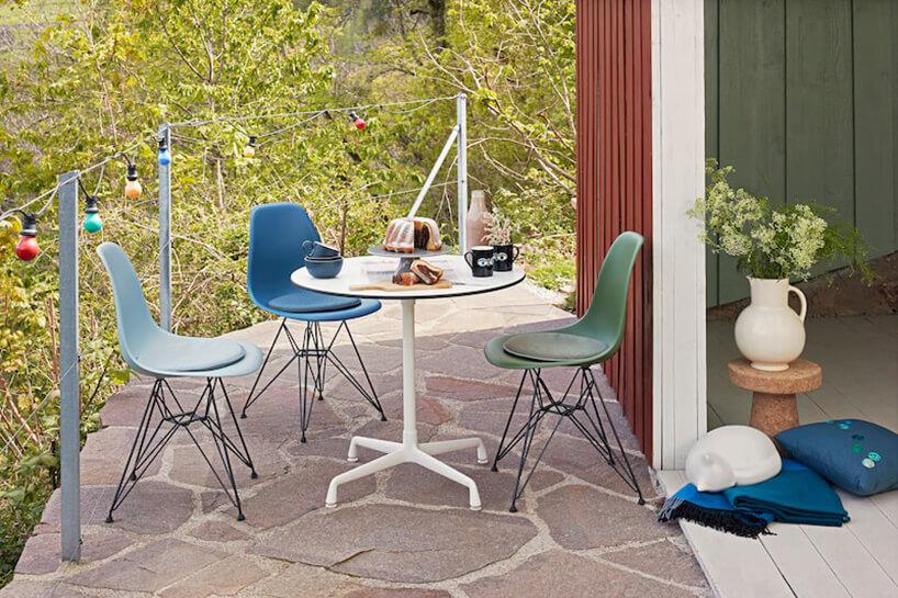 mały kamienny taras ztrzem kolorowym krzesełkami ibiałym stolikiem na tle drzew