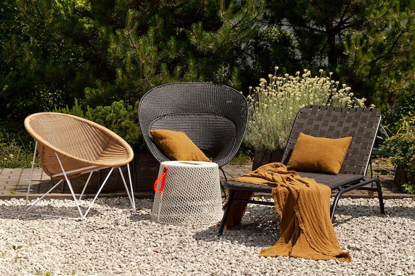 trzy rożne eleganckie krzesła zewnętrzne Bertoia Side Chair od Knoll na kamienistym tarasie na tle iglastych drzew