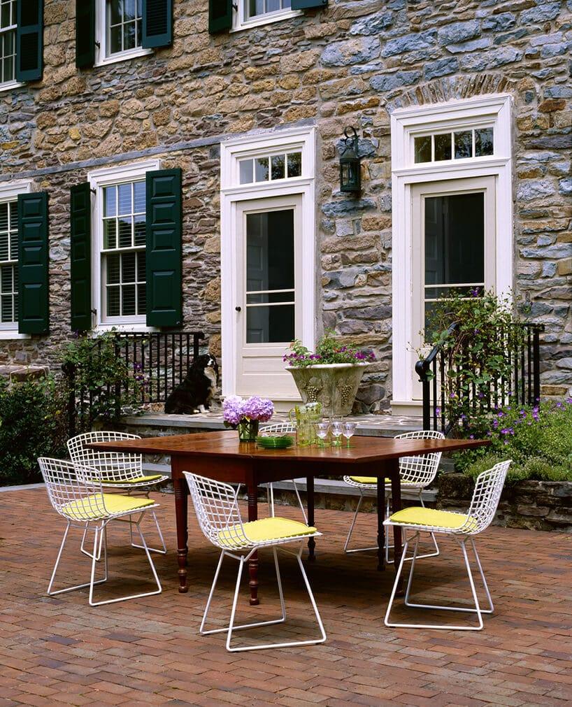 białe krzesła wkratkę zdrutu przy drewnianym stole na tle kamienistej ściany rezydencji