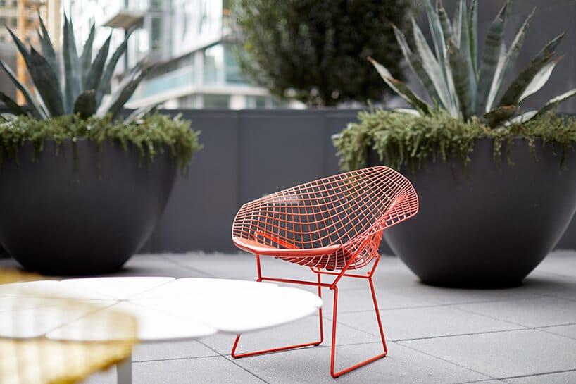 czerwone krzesło zmetlaowego drutu na szarym tarasie na tle dwóch szarych donic