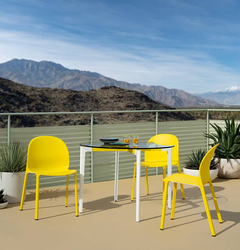 trzy zółte krzesłą przy białym stoliku ze szklanym okrągłym blatem