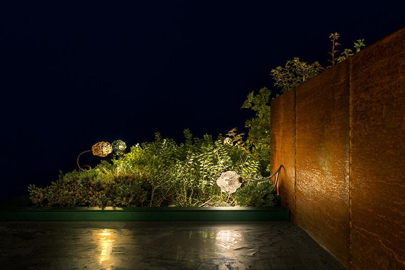wyjątkowe lampy Catellani & Smith od Mood Design na tarasie ze ścianą zmetalowej zardzewiałej płyty