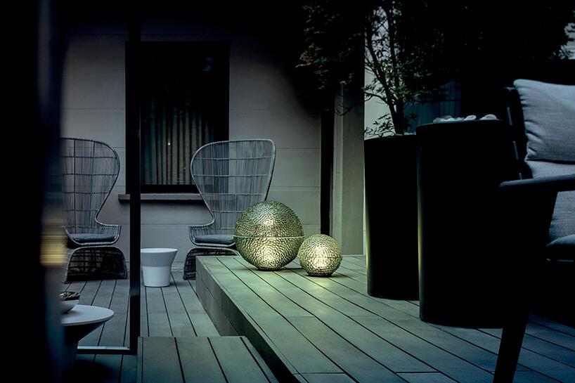 dwie kuliste lampy 12 Catellani & Smith od Mood Design na drewnianym tarasie