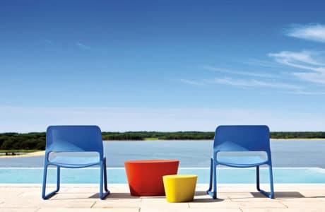 dwa niebieskie krzesła obok dwóch cylindrycznych stolików na tle basenu i lasu w oddali