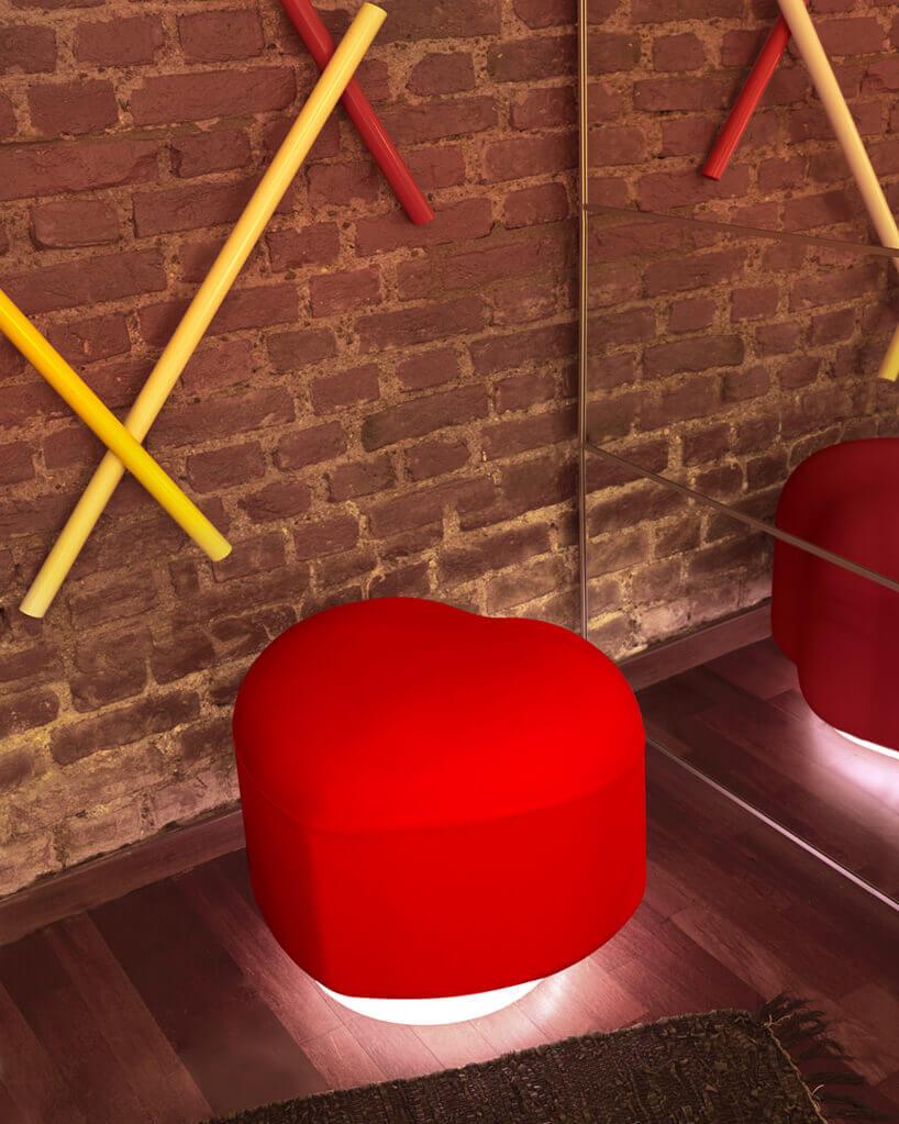 czerwona pufa wkształcie sreca Lempi od Slide projektu Giò Colonna Romano zpodświetloną podstawą na tle ceglanej ściany