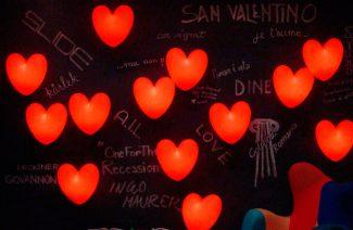 czarna ściana z napisami kredowymi i czerwonymi świecącymi sercami