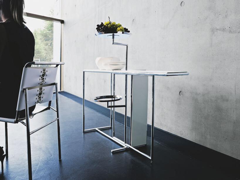 biały stolik herbaciany na tle betonowej ściany iciemnej podłogi