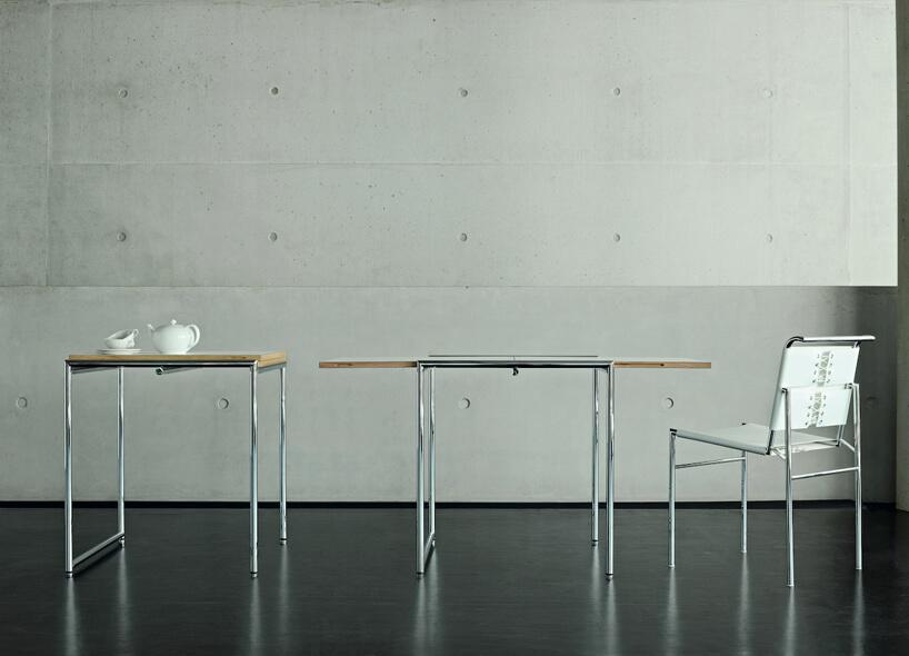 stolik rozkładany wwersji złożonej irozłonej zmetalowym stelażem obok krzesła zbiałym siedziskiem ioparciem