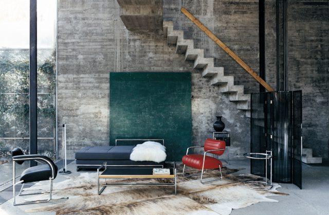 łóżko i dwa fotele z metalowymi szkieletami w wysokim wnętrzu z surowym betonowym klimatem