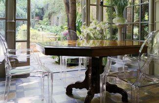 plastikowe przeźroczyste krzesła przy drewnianym masywnym stole