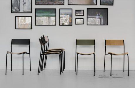 krzesła na tle szarej ściany z obrazami