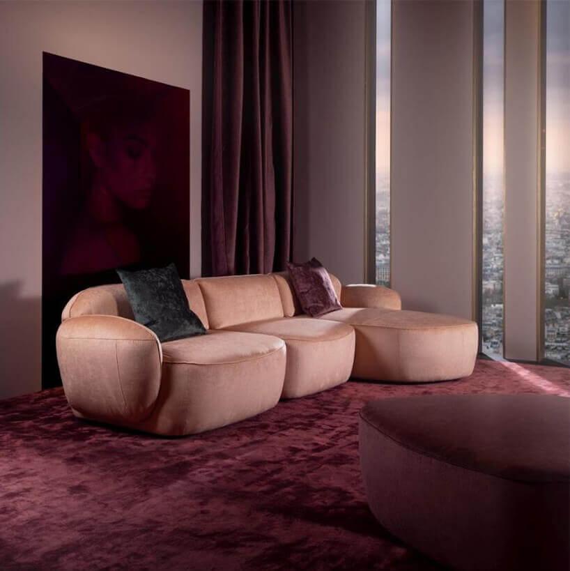 Sofa Blues od mti furninova na wiśniowym dywanie wpokoju zwidokiem na miasto