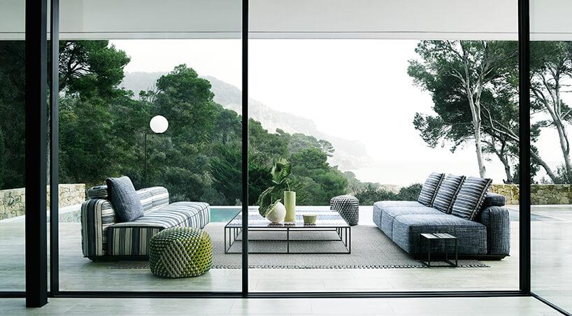 szara ibiało zielona sofa zewnętrzna Hybrid od B&B Italia na kamiennym tarasie zwidokiem na las