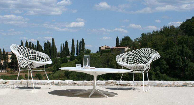 biały zestaw mebli ogrodowych od Knoll dwa siatkowe krzesła zniskim szerokim stolikiem na kamiennym tarasie