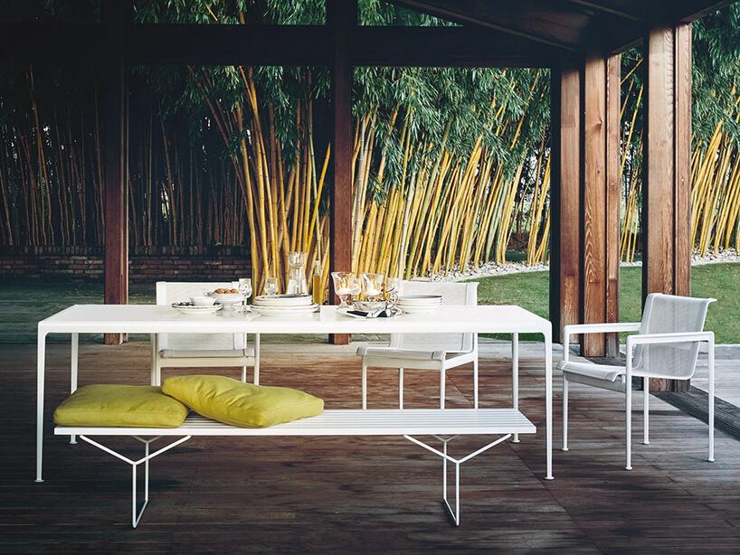 biały zestaw mebli ogrodowych od Knoll długa ławka ztrzema krzesłami przy długim stole pod drewnianym dachem