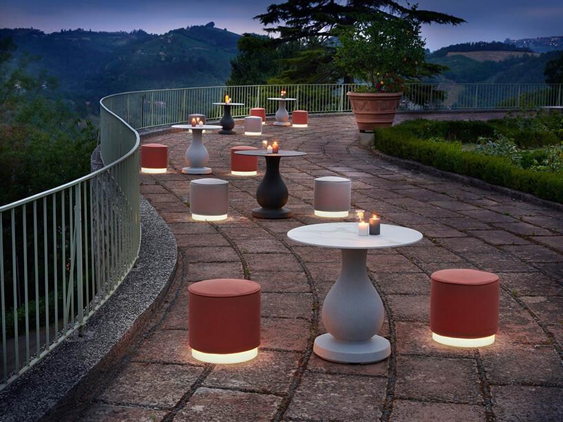 zestaw mebli ogrodowych Ottocento od SLIDE projektu Paola Navone dwa siedziska zpodświetloną podstawą przy małych stolikach na kamiennym tarasie