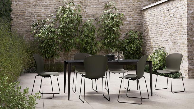 taras ogrodowy otoczony ścianami zkamienną podłogą iczarnym zestawem ogrodowym