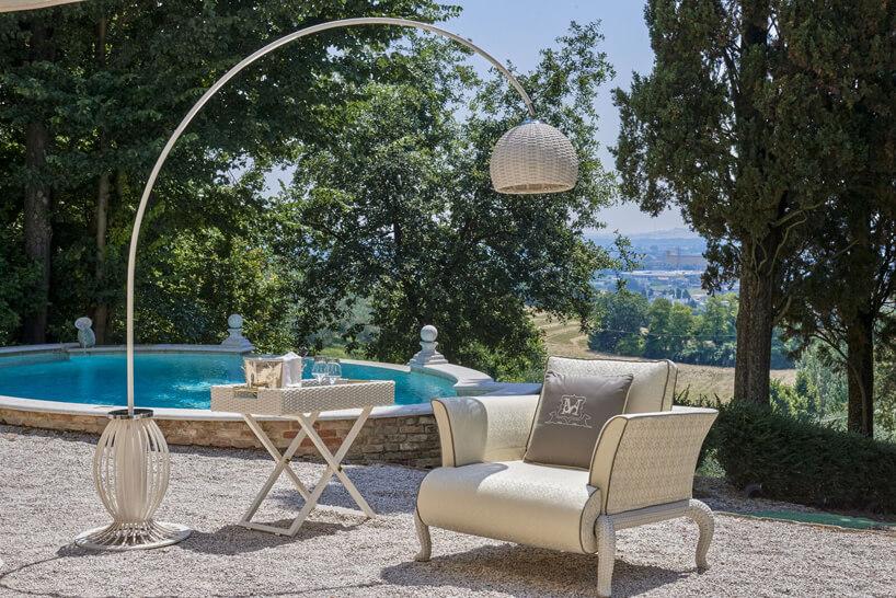 ekskluzywne meble ogrodowe Canopo od Samuele Mazza beżowy fotel zwysoką lampą istolikiem na tle basenu