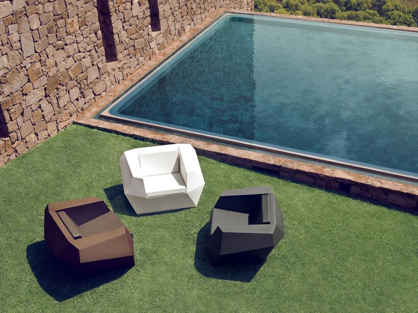 trzy ekskluzywne fotele ogrodowe zkolekcji projektu Ramon Esteve dla Vondom obok kamiennej ściany ibasenu