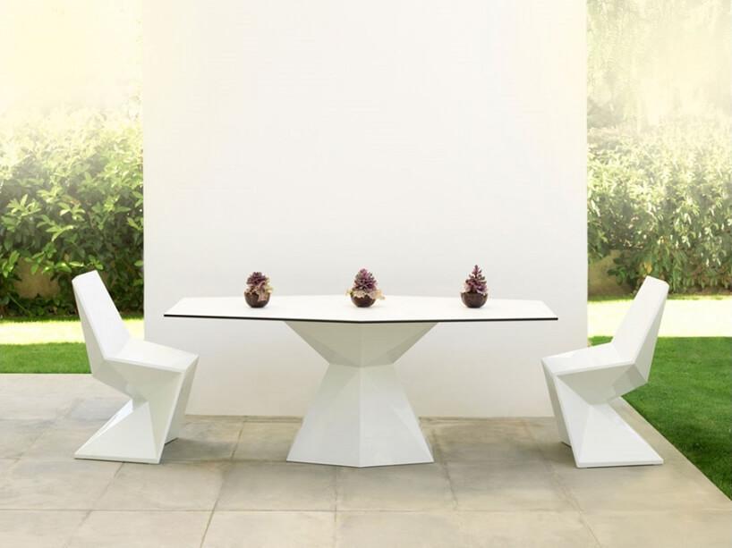 białe ekskluzywne meble ogrodowe zkolekcji Vertex projektu Karim Rashid dla Vondom dwa krzesła onietypowych kształtach przy stole zczarną ramką blatu