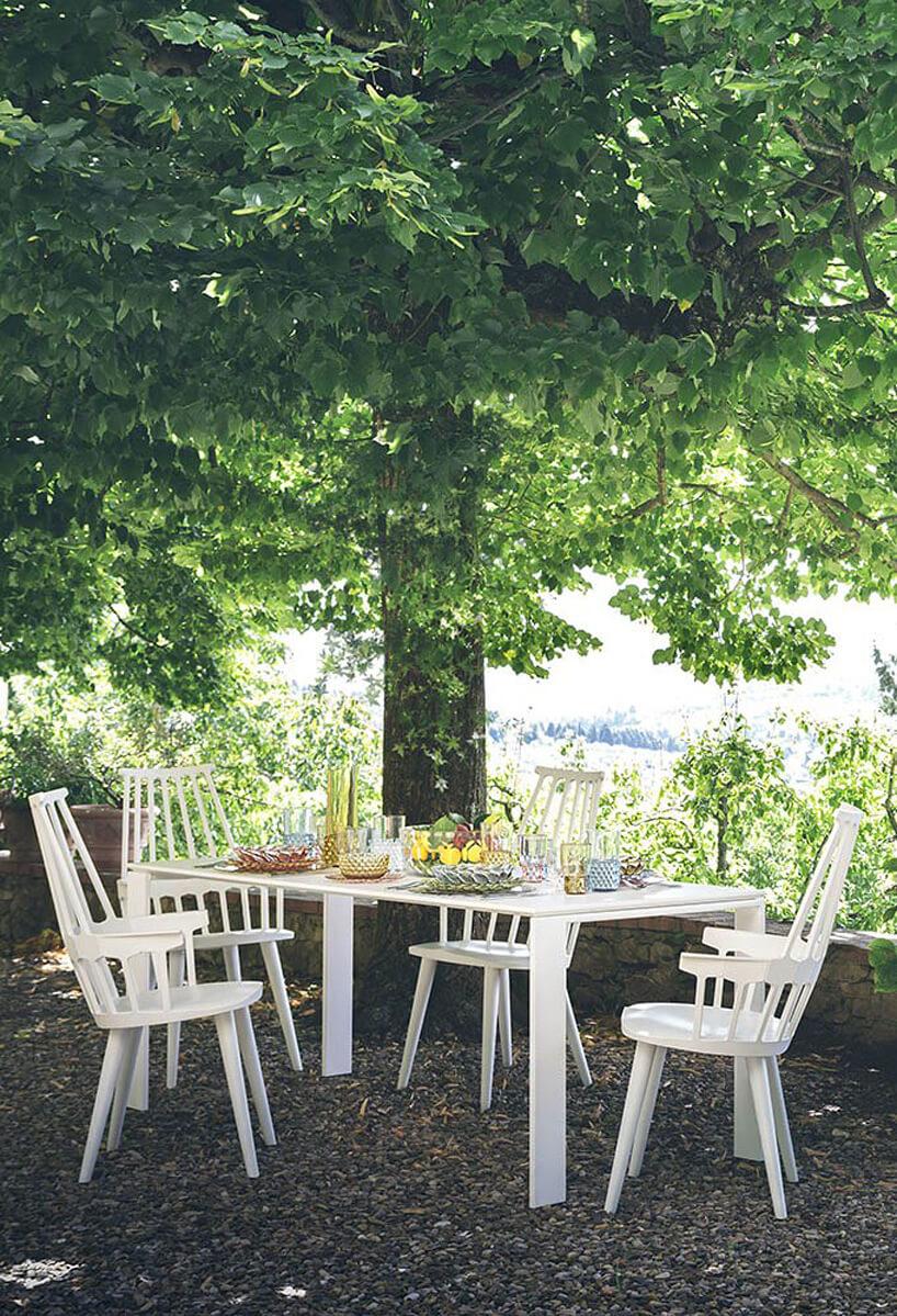 biały stół ogrodowy Four od Kartell, zczterem białymi krzesłami na tarasie wcieniu drzewa