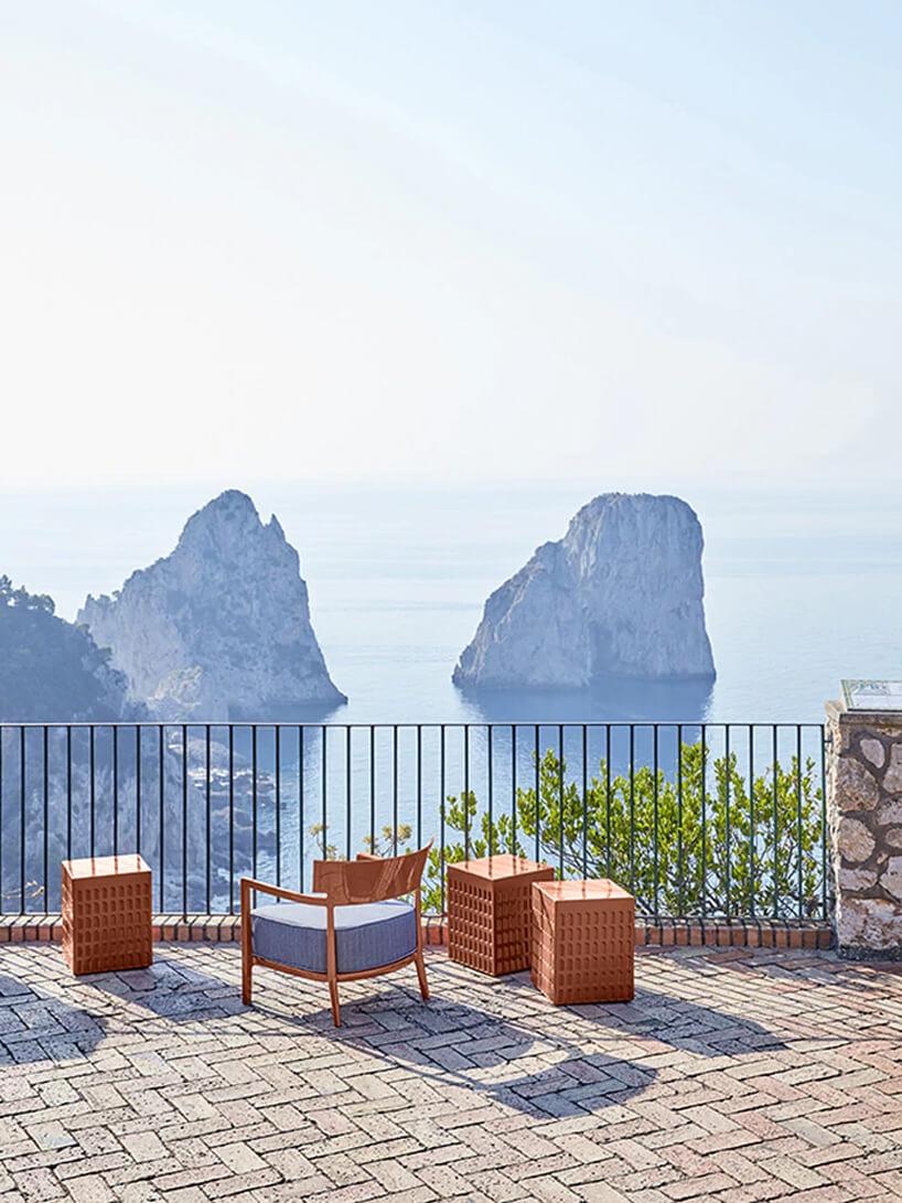 brązowe ekskluzywne meble ogrodowe od Kartell małe prostokątne stoliki ikrzesło zniebieską poduszką na kamiennym tarasie na tle morza