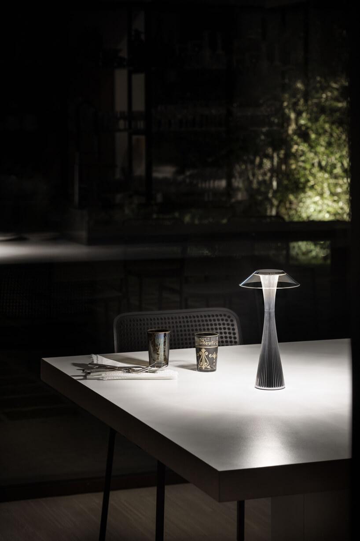 mała ekskluzywna czarna lampa ogrodowa Space Chrom od Kartell na dużym stole zdwoma kubkami nocą