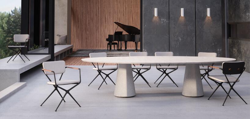 ekskluzywne meble ogrodowe Conix iExes od Royal Botania duży szary stół na masywnych dwóch nogach zszarymi krzesłami na czarnych metalowych stelażach na przestronnym tarasie