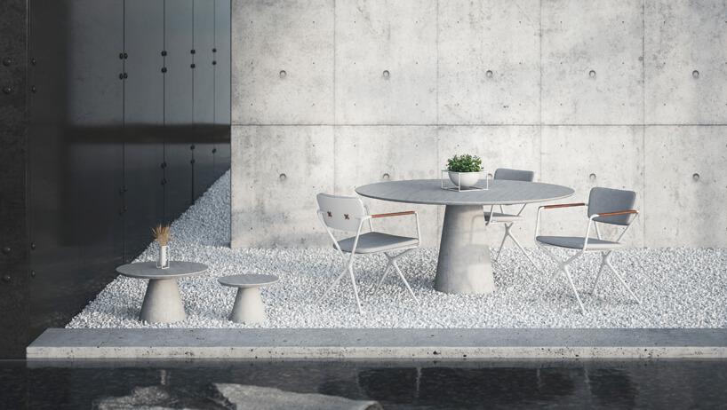 szare ekskluzywne meble ogrodowe Conix iExes od Royal Botania okrągły stół zdwoma szarymi krzesłami idwoma małymi stolikami na kamienistym tarasie
