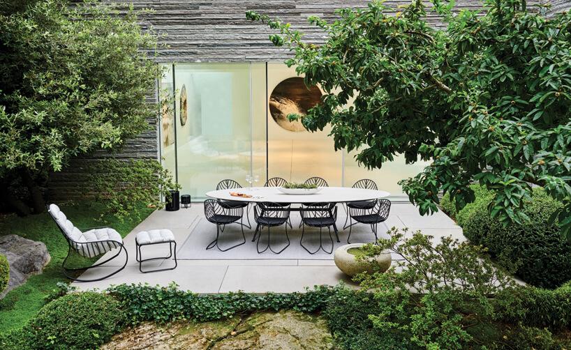 ekskluzywne meble ogrodowe Exes iFolia od Royal Botania biały owalny stół na czarnych metalowych nogach zczarnymi krzesłami zcienkich prętów na małym tarasie