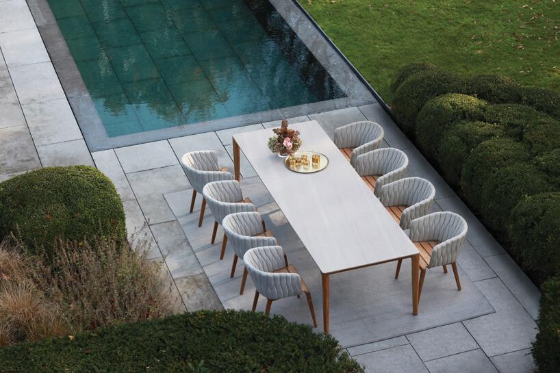 ekskluzywne meble ogrodowe Calypso od Royal Botania drewniany stół zbiałym kwadratowym blatem zeleganckim drenianymi krzesłami zjasnymi plisowanymi oparciami na tarasie nad basenem